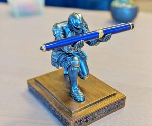 The Executive Knight Pen Holder is a bowing knight, hands raised to hold your modern quill. Your pen is held aloft, so you never have to figure out which stack