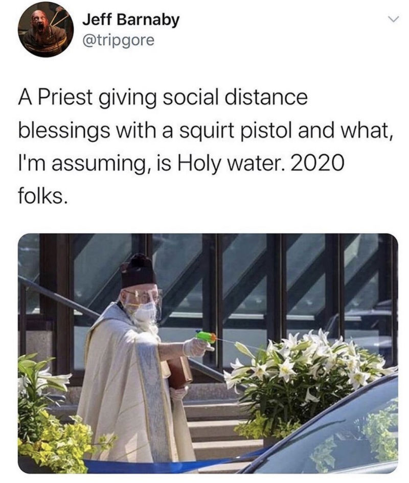 priest giving social distance blessings with a squirt gun