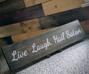 "Live. Laugh. Hail Satan! Wood Sign – Does worshiping the dark Lord and true savior bring happiness and fulfillment to your life? Let the world know with this ""Live, Laugh, Hail"