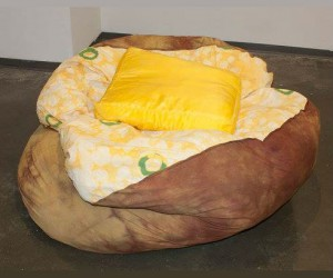 This baked potato bean bag chair comes complete with a satin butter shaped pillow and decorative chives.